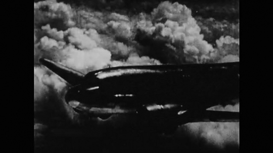 UNITED STATES: 1940s: Mainliner plane flies in clouds.  Plane comes in to land. Man waves plane into parking place.