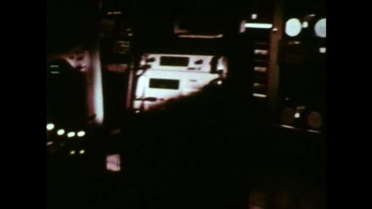 UNITED STATES 1960s: Tracking shot through control room at space flight center / Low angle shot, equipment lowers into hands / High angle shot, man lowers equipment to workers.