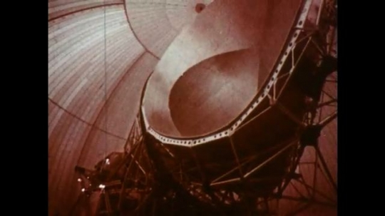 UNITED STATES 1960s: Satellite dish turning / View of dome, tilt up to sky / Jet flying / Underside of jet / Equipment dropping from jet.