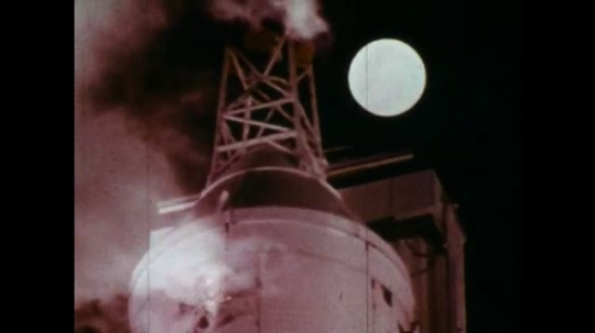 UNITED STATES 1960s: Nose of rocket, moon in background / View of moon, smoke / Distorted view, astronaut walking / Astronaut walks into chamber / Equipment spinning / Closer view of equipment.