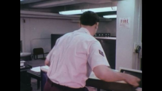 UNITED STATES 1970s: Man puts cards on table / Hands stack cards / Hands puts cards in machine / Tape reel turns / Zoom in on tape reel.