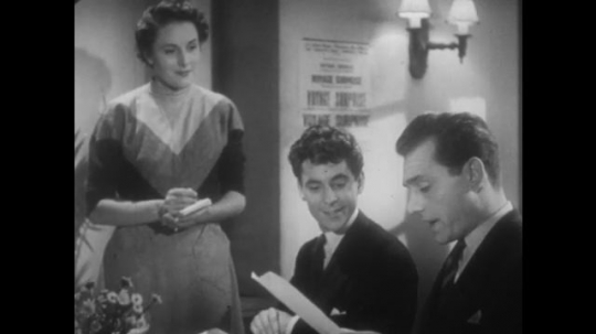 EUROPE, 1940s: Waitress asks men what they would like to order. Man reads menu choice to waitress. Waitress writes down orders. Waitress leaves table.