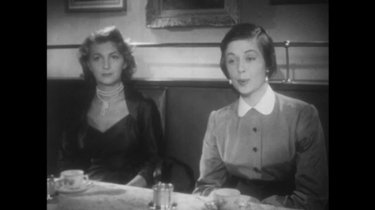 EUROPE, 1940s: Two ladies at a restaurant table. Four diners drink coffee after meal in restaurant. Lady checks hair in mirror at restaurant table.