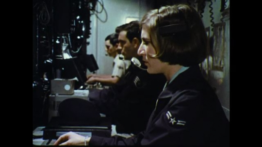 UNITED STATES: 1960s: USAF lady works on switchboard. Man in sunglasses looks upwards. USAF lady at work. Man talks to camera