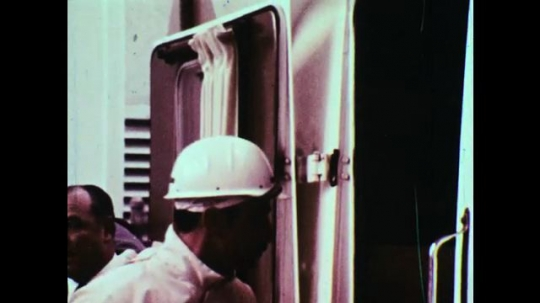 UNITED STATES, 1960s: NASA specialist enters launch pad elevator with astronauts. Man closes elevator cage as astronauts prepare to enter rocket. Space shuttle elevator going up.