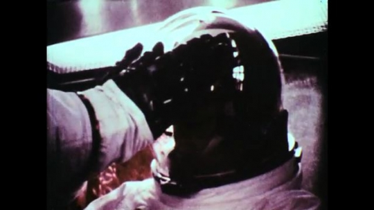 UNITED STATES, 1960s: NASA technician presses hands over helmet of astronaut. NASA astronaut leans in over camera and smiles. NASA team help astronaut climb in to space capsule. Man smiling at crew.