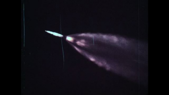 UNITED STATES, 1960s: Flames fading as NASA rocket travel up through sky towards space. Rocket separates from unit.