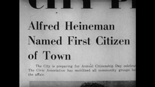 United States, 1940s: Article headline reads 'Alfred Heineman Named First Citizen of Town'. Man shows boy a story in the newspaper.
