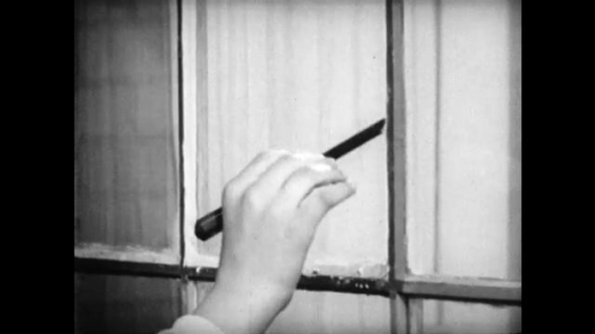 United States, 1940s: Boy uses tools to repair broken pane of glass in window. Repaired window.