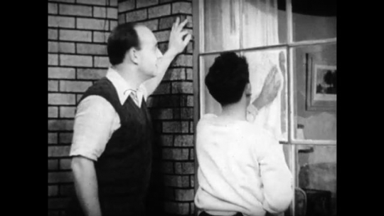 United States, 1940s: Boy polishes window pane with cloth. Man smiles as boy repairs window pane. Man and boy enter office and walk to desk.
