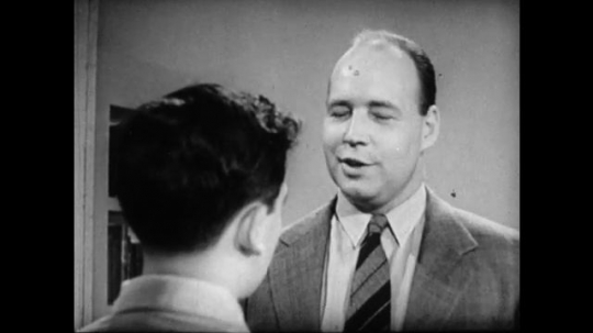 United States, 1940s: Man smiles as he talks with boy.