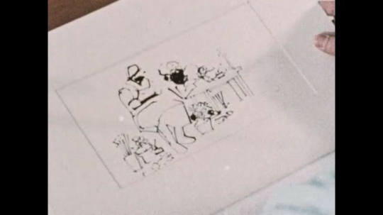 UNITED STATES: 1970s: Drawing on paper. Man places tracing paper on top of drawing. Papers on a table.