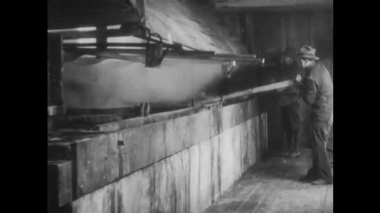 UNITED STATES: 1950s: Man stirring hot liquid at mill. Man uses large spoon to transfer hot liquid.