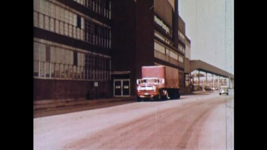 UNITED STATES 1960s: Truck drives next to factory / Wipe cut, train driving / Iris out, close up of poster, zoom out on poster.