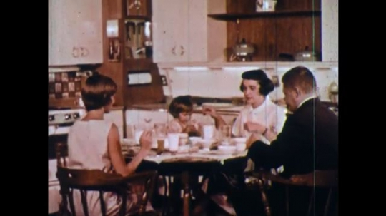 UNITED STATES 1960s: Family eating at table, man exits / High angle view, people in TV studio / Pan to TV camera / Wipe cut, kids in class with teacher.