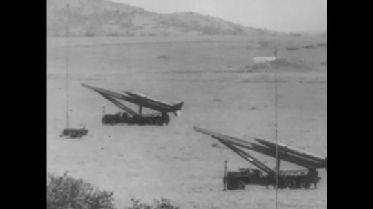 EUROPE, 1950s: Rockets being launched from guns on ground. Men in armed tank. Rocket flying through the air. Soldiers using a metal detector. Soldier removes land mine from soil.
