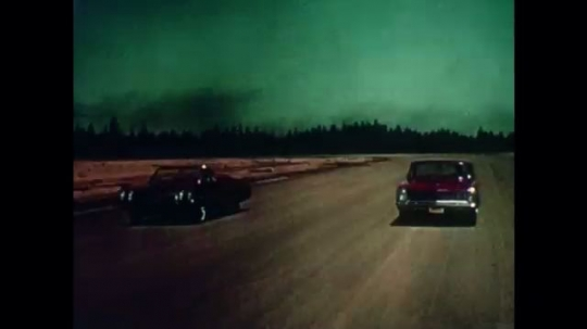 UNITED STATES, 1965: Two cars drive side by side, third one pops up, then the other two disappear.