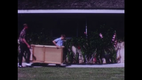 UNITED STATES: Man and boy carry large pieces of wood into house.