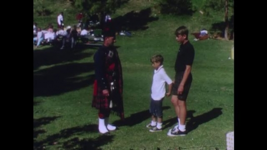 UNITED STATES: Man in kilt shakes hands with boys.
