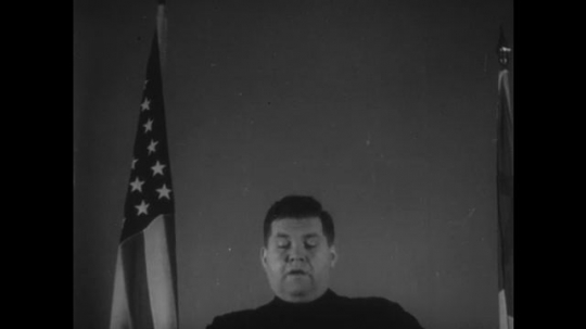 UNITED STATES, 1940s: Church Minister speaks as he stands next to American flag. Church full of people listening to sermon.