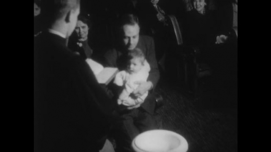 UNITED STATES, 1940s: Man holds baby during baptism in church. Lady typing on a typewriter. 'Management of Church Business' Title. Man writing notes at a desk.