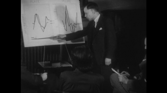 UNITED STATES, 1940s: Man pointing at graph with stick. Church Minister speaking into a Microphone.
