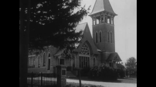 UNITED STATES, 1940s: View of a Church. Clouds in sky over church. Church tower. Writing engraved over church door.
