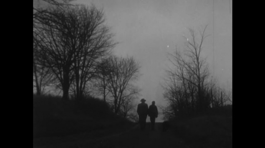 UNITED STATES, 1940s: People walking down country road on winters day. Church spire.