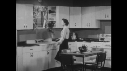 UNITED STATES 1940s: Lady walks to kitchen window. Lady takes apron from kitchen drawer. Lady puts on apron