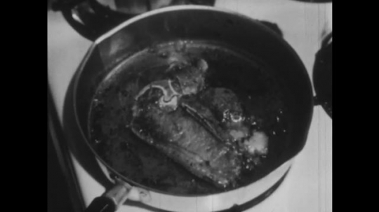 UNITED STATES 1940s:Meat sizzling in a pan. Clock on a wall. Potatoes boiling in a pan.