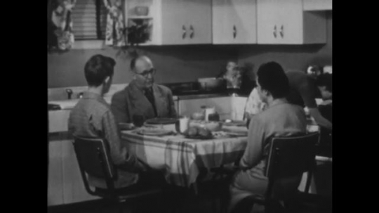 UNITED STATES 1940s: lady takes food out of the oven as guests sit at table. Man carves meat at table.
