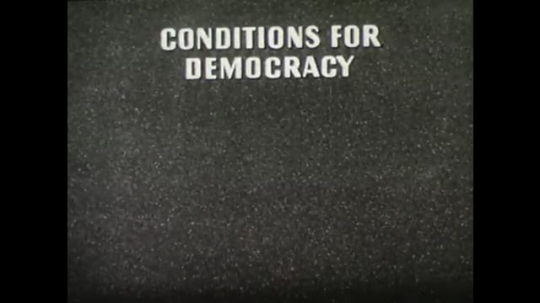 United States, 1940s: Title credit showing the conditions for democracy. Image of economic balance. Text book writing and illustration.