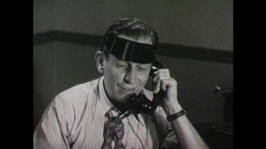 United States, 1940s: Newspaper man sits at desk and talks on telephone. Man on telephone shakes his head. Man talking on telephone. Buildings in a city.