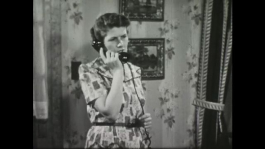 UNITED STATES: 1950s: Lady talks on telephone. Man walks out to car. Man gets in car. Ladies talk in kitchen.