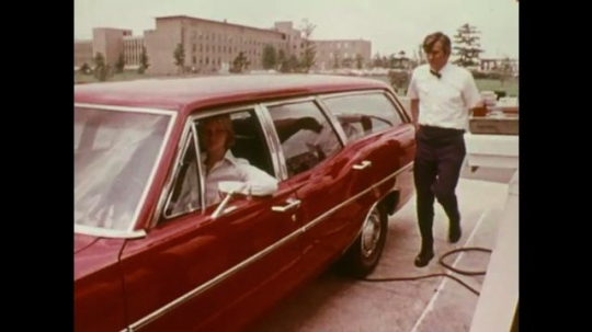 UNITED STATES: Attendant checks battery on red Station Wagon.