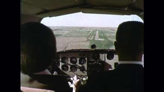 UNITED STATES: 1970s: Plane coming in to land. View from behind pilot and co pilot as plane lands.