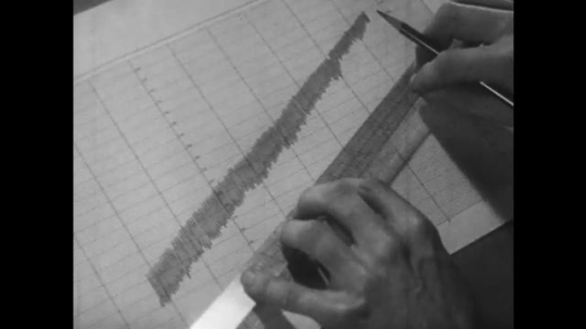 USA, 1950s: Man using a ruler to draw a line on a graph. Man measuring oxygen use in an experiment and writing it on a form. Basal metabolic chart. Thermometer reading.