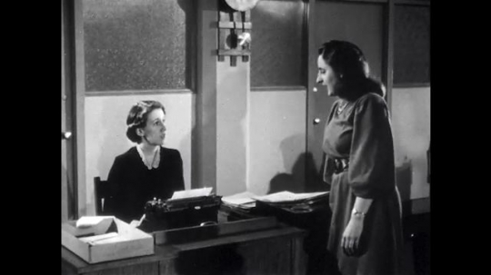 UNITED STATES: 1940s: Woman talks to lady at desk. Lady shows dress pattern in magazine to colleague.