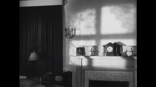 UNITED STATES: 1940s: Lady arrives home. Lady plates up food as girl arrives home. Lady takes off hat.