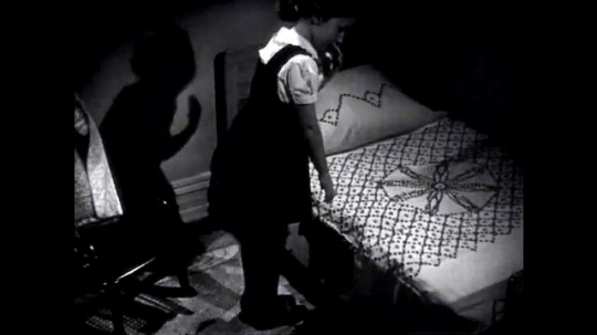 UNITED STATES: 1940s: Girl gets ready for school. Girl tidies bed and shoes.