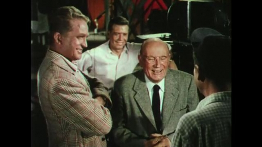 UNITED STATES: 1950s: Men gathered in film studio share a joke. Men gather around and listen in film studio. Man gets up and walks away. Man walks over to model and picks it up.