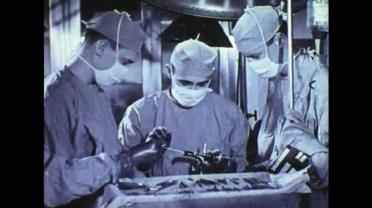 UNITED STATES: 1950s: Surgeons performing operation on patient in theatre. Machine records brain waves as brain is exposed during operation. Brain waves being recorded on chart.