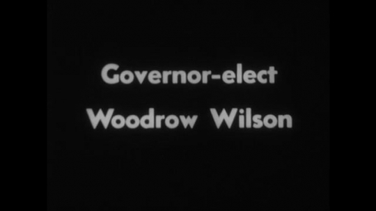 UNITED STATES 1890s: Intertitle / Woodrow Wilson seated, surrounded by men / Intertitle / Men with cameras / Wilson talking with men.