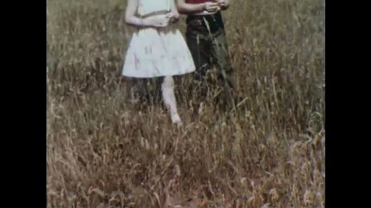UNITED STATES, 1956: Camera focuses on legs of boy and girl as they walk through field.