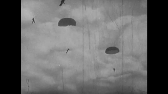EUROPE, 1930s: Men dangling from parachutes in the sky. View of back of plane as paratroopers jump. Trainee paratroopers land on ground after jump from plane.