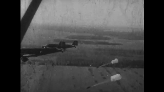 EUROPE, 1930s: View of back of plane as German paratroopers jump and open parachutes. View of ground from plane as paratroopers land.