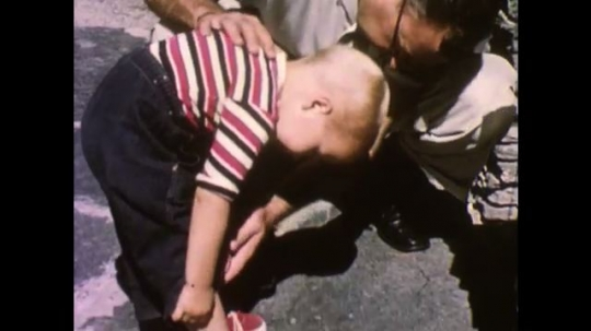 UNITED STATES, 1940s: Toddler rubbing his leg. Man rubs toddler's leg. Ants on a sandwich on the ground. Baby crying.