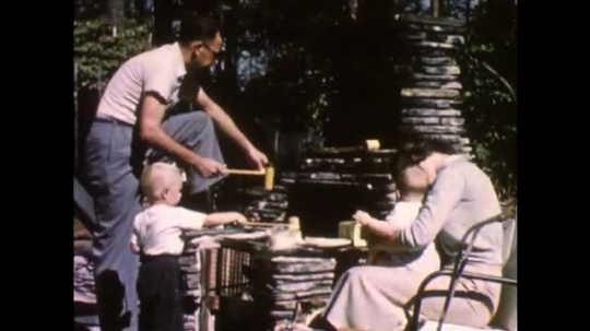 UNITED STATES, 1940s: Man, lady and children enjoy barbecue in garden. Young boy helps father with the outdoor grill.