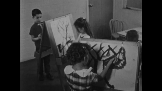 UNITED STATES: 1950s: Children painting on easels. Boy painting picture of a tree.