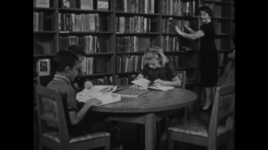 UNITED STATES: 1950s: Children sit at table in library and read books. Girl asks librarian a question.